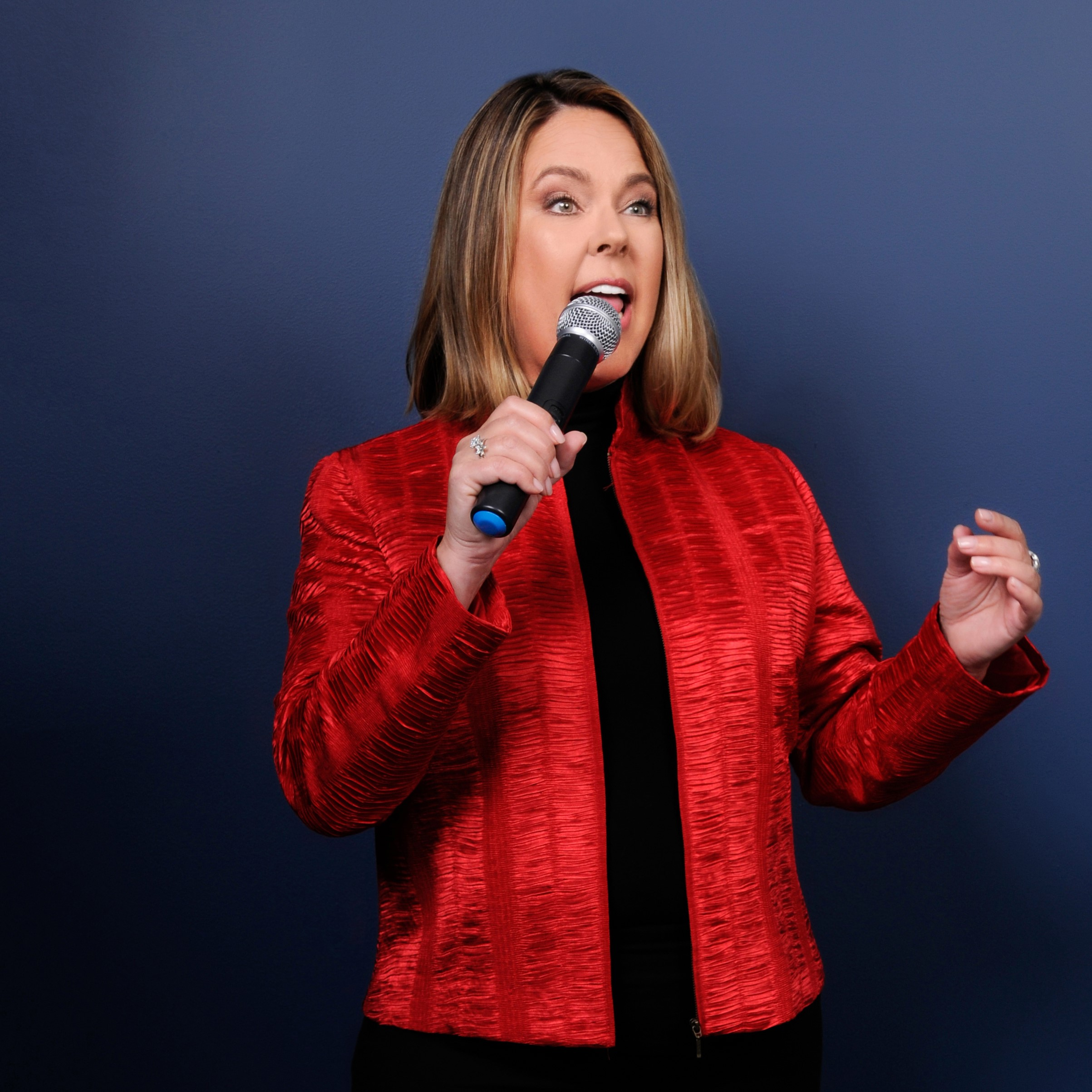 Rachel Cartwright speaking on blue background in red jacket